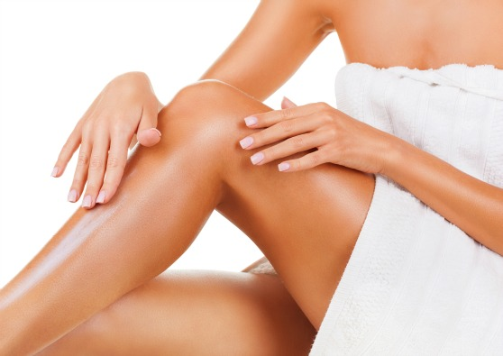 a woman applying lotion on her legs